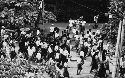 FILE - Despite martial law, Buddhist monks and students carry a flag in protest against the government, Aug. 9, 1988, in downtown Rangoon.