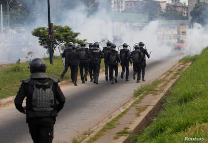 Ivory Coast riot policemen disperse opposition supporters with tear gas during a march to protest against Ivory Coast's President Alassane Ouattara's new constitution in Abidjan, Ivory Coast, October 20, 2016.