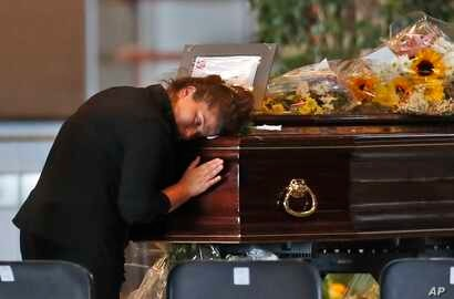 A woman mourns a victim of a collapsed highway bridge, at the Fiera di Genova exhibition center, where some of the coffins are laid in state, in Genoa, Italy. A state funeral for most of the victims will take place in Genoa on Saturday.