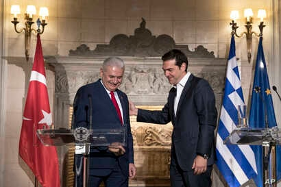 FILE - Greek Prime Minister Alexis Tsipras, right, shows the way to his Turkish counterpart Binali Yildirim, at the end of their joint news conference in Athens, Monday June 19, 2017.