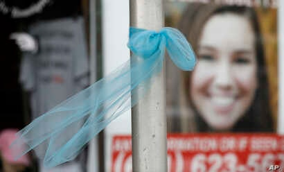 A ribbon for missing University of Iowa student Mollie Tibbetts hangs on a light post, Aug. 21, 2018, in Brooklyn, Iowa.