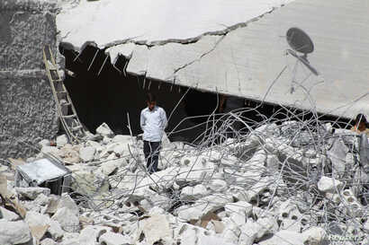 A resident walks upon the debris of buildings which were damaged in what activists say was one of Tuesday's U.S. air strikes in Kfredrian, Idlib province September 24, 2014.