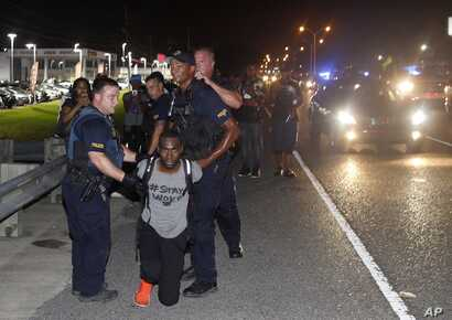 Police arrest Black Lives Matter leader DeRay McKesson during a protest along Airline Highway, a major road that passes in front of the Baton Rouge Police Department headquarters on July 9, 2016, in Baton Rouge, La. (AP)