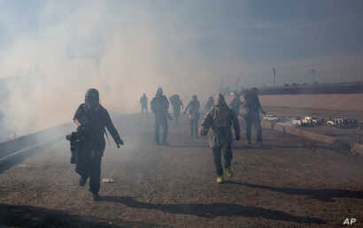 Migrants run from tear gas launched by U.S. agents, amid photojournalists covering the Mexico-U.S. border, after a group of migrants got past Mexican police at the Chaparral crossing in Tijuana, Mexico, Sunday, Nov. 25, 2018.