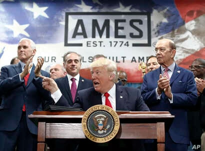 President Donald Trump, joined by Vice President Mike Pence, (from left) Secretary of Veterans Affairs David Shulkin, and Wilbur Ross United States Secretary of Commerce, signs an Executive Order on the Establishment of Office of Trade and Manufactur...