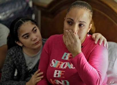 In this Jan. 23, 2018 photo, Leslie Rivera is comforted by her daughter Yandeliz during an interview in their hotel room at the Rodeway Inn in Tampa, Florida, where they're living after Hurricane Maria destroyed their home in Puerto Rico.