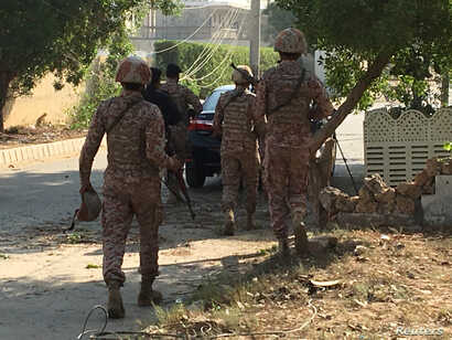 Paramilitary forces and police are seen during an attack on the Chinese embassy, where blasts and shots are heard, in Karachi, Pakistan, Nov. 23, 2018.