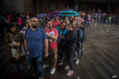 People queue to vote at a school listed to be a polling station by the Catalan government in Barcelona, Spain, Oct. 1, 2017.
