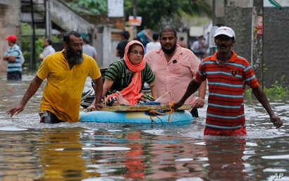 An elderly Sri Lankan woman is pulled on a makeshift raft at a flooded area in Colombo, Sri Lanka, May 17, 2016. T