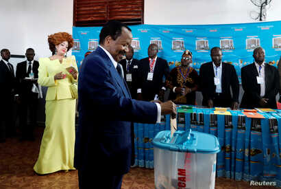Cameroonian President Paul Biya casts his ballot while his wife Chantal Biya watches at a polling station during the presidential election in Yaounde, Cameroon, Oct. 7, 2018.
