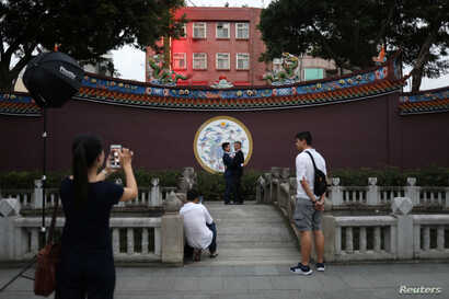 John Sugden and Kao Shaochun have their pre-wedding photos taken by Austin Haung, 32, as Lin Chinxuan, right, 29, stands by, in Taipei, Taiwan, Nov. 11, 2018.