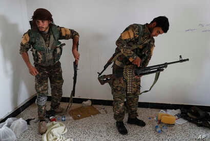 An Arab fighter, left, and Kurdish fighter, right, hold their weapons as they prepare to move to the front line to battle against the Islamic State militants, in Raqqa, northeast Syria, July 22, 2017.