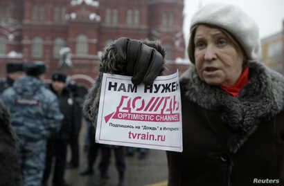 """FILE - A protester holds a flyer reading """"We need Dozhd"""" during a rally in support of the independent television station Dozhd (TV Rain), in Moscow, February 8, 2014."""