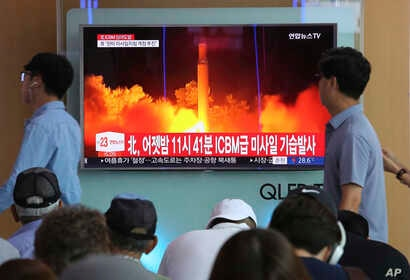 People watch a TV news program showing an image of North Korea's latest test launch of an intercontinental ballistic missile at the Seoul Railway Station in Seoul, South Korea, July 29, 2017.