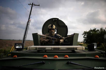 An agent with the U.S. Border Patrol Tactical Unit (BORTAC) holds his weapon from an armored vehicle ahead of exercises in Mission, Texas,, Nov. 8, 2018.