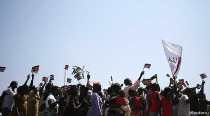 People wave South Sudanese flags as they celebrate referendum results in town of Abyei, Oct. 31, 2013.