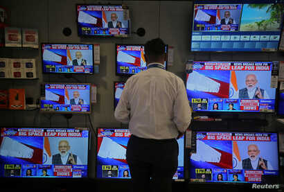 A salesman watches Prime Minister Narendra Modi addressing to the nation, on TV screens inside a showroom in Mumbai, India, March 27, 2019.
