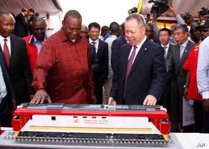 Kenyan President Uhuru Kenyatta, left, looks at a model of a locomotive with Chen Fenjian president of CCC during the unveiling of a cargo train at the Mombasa, Kenya.