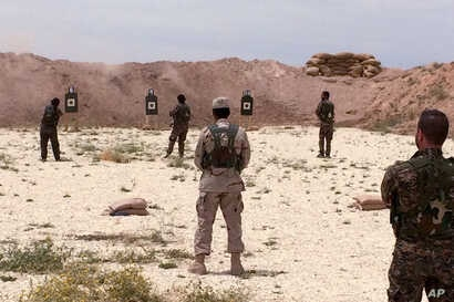 Syrian Arab trainees practice firing their small arms at an undisclosed training range in northern Syria on  May 21, 2016.