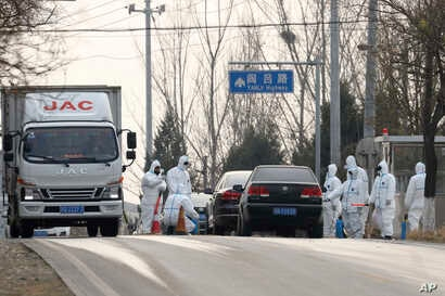 Workers disinfect passing vehicles in an area having the latest incident of African swine flu outbreak on the outskirts of Beijing, China, Friday, Nov. 23, 2018.
