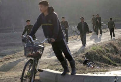 Some North Korean men walk while others push bicycles along a highway at the end of a work day in Pyongyang, April 11, 2017, North Korea. North Korea will mark the 105th anniversary of the birth of the late leader Kim Il Sung on April 15.