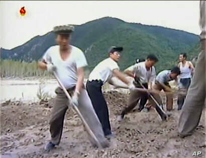In this undated image from video distributed on Sept. 12, 2016, by North Korean broadcaster KRT, North Korean workers build levees along a river bank.