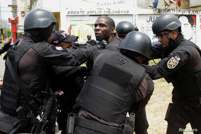 A man is detained by police as he takes part in a protest against the unfinished public works in Colon, Panama, March 13, 2018.