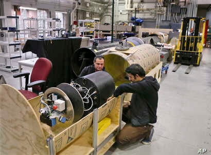 David Kohandash, left, and Mohammad Mousaei work on a robot in the robotics institute at Carnegie-Mellon University in Pittsburgh, April 4, 2018.