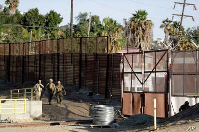 Marines patrol during work to fortify the border structure that separates Tijuana, Mexico, behind, and San Diego, near the San Ysidro Port of Entry, Nov. 9, 2018, in San Diego.