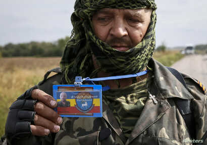FILE - A pro-Russian separatist shows his identification card to Ukrainian journalists at a checkpoint near the town of Slavyanoserbsk, Luhansk region, eastern Ukraine, Sept. 10, 2014. Some in Ukraine see journalists operating in rebel-held areas as ...