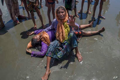 A Rohingya Muslim woman, who crossed over from Myanmar into Bangladesh, shouts for help as a relative lies unconscious after the boat they were traveling in capsized minutes before reaching shore at Shah Porir Dwip, Bangladesh, Thursday, Sept. 14, 20...