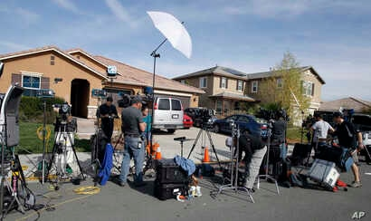 Members of the media work outside the home where police arrested a couple accused of holding 13 children captive, in Perris, Calif.