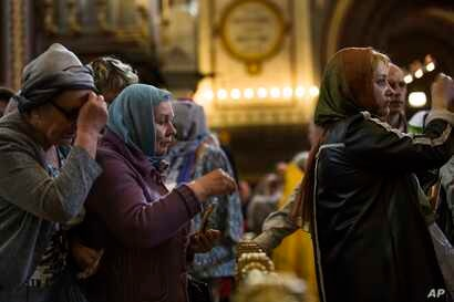 In this photo taken on Friday, May 26, 2017, Russian Orthodox believers cross themselves as they line up to kiss the relics of Saint Nicholas in the Christ the Savior Cathedral in Moscow, Russia.