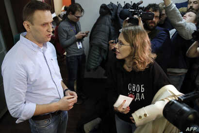 Presidential candidate and Russian TV journalist Ksenia Sobchak, right, listens to opposition leader Alexei Navalny as she visits his office in Moscow, March 18, 2018