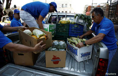 Men carry boxes with agricultural products donated for needy people by fruit and vegetables vendors from markets as part of Holy Week in San Jose, Costa Rica, April 12, 2017.
