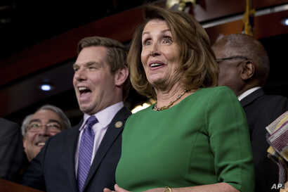 House Minority Leader Nancy Pelosi of Calif. (right) accompanied by Rep. G. K. Butterfield, D-N.C. (left) and Rep. Eric Swalwell, D-Calif. (second from left) as they joke while speaking at a news conference on Capitol Hill in Washington, March 24, 20...