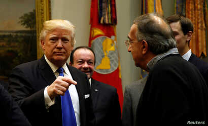 President Donald Trump greets Fiat Chrysler CEO Sergio Marchionne, right, as he hosts a meeting with U.S. auto industry CEOs at the White House in Washington, Jan. 24, 2017.