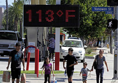 FILE - Pedestrians walk past a digital thermometer reading 113 degrees Fahrenheit (45 degrees Celsius) in the Canoga Park section of Los Angeles, Aug. 15, 2015.