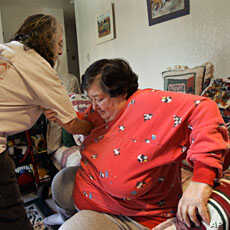 Sharon Pribble (R) is helped to her feet by home care worker Vernita Bellew in Pribble's home in Olympia, Washington (File)