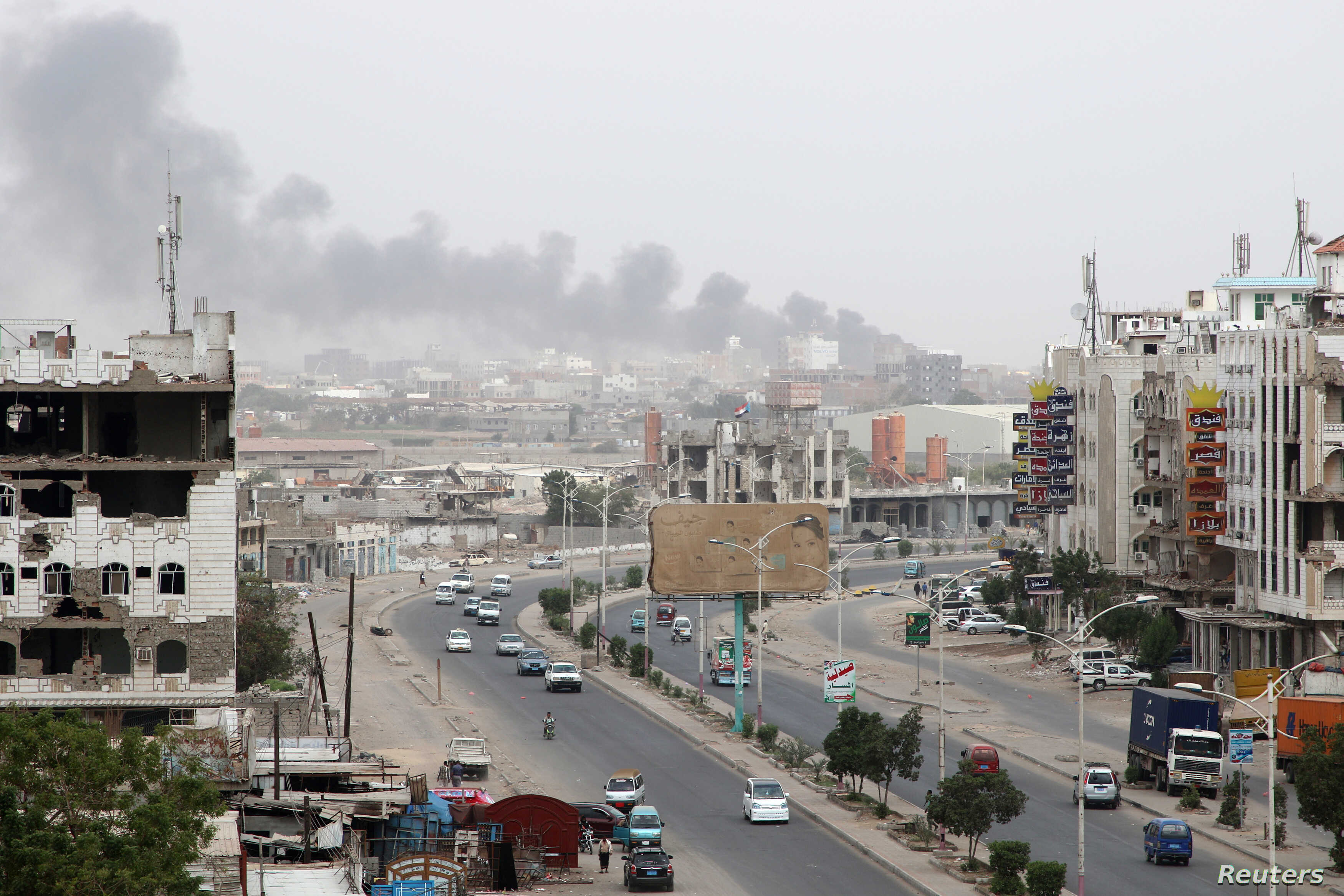 Smoke billows from a car parts store hit by shelling during the conflict in the port city of Aden, Yemen Jan. 31, 2018.