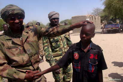 FILE - A Chadian soldier embraces a former child soldier of insurgent group Boko Haram in Ngouboua, Chad, April 22, 2015. The young men said they were Chadian nationals forced to join Boko Haram while studying the Quran in Nigeria, and that they esca...