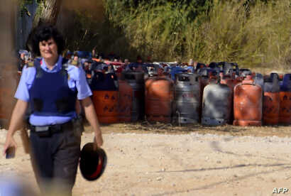A policewoman walks with dozen of gas bottles in background in Alcanar during a search linked to the Barcelona and Cambrils attacks on the site of an explosion on August 18, 2017.