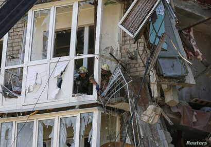 Rescuers work at a shattered five-storey building, which was damaged by a recent shelling, in the eastern Ukrainian town of Slaviansk July 16, 2014. Fighting raged in Ukraine's east on Wednesday when separatists tried to break through the lines of go...