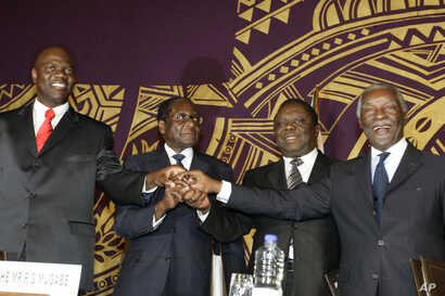 FILE - Officials join hands at the signing of the power-sharing deal in Harare, Zimbabwe, Sept, 15, 2008. From left: Arthur Mutmbara, deputy prime minster; Robert Mugabe, president; Morgan Tsvangirai, prime minster; and Thabo Mbeki, South Africa's pr...