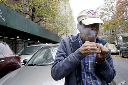 Luis Torres smokes a cigarette outside the New York City Housing Authority's Chelsea-Elliot Houses where he lives, Nov. 12, 2015, in New York.