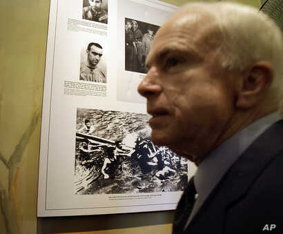FILE - U.S. Sen. John McCain, R-Ariz, is seen during a tour of Hoa Lo Prison site, Hanoi, April 8, 2009.  The photo behind McCain is that the Hanoi army and people pull out McCain out of Truc Back Lake on Oct. 26, 1967 after his plane was shot down. ...