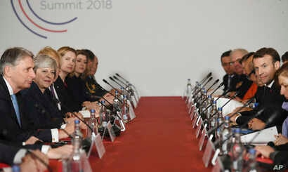 Britain's Prime Minister Theresa May (2nd-L) and French President Emmanuel Macron (2nd-R) sit with their delegations during UK-France summit talks at the Royal Military Academy Sandhurst, in Camberley, England, Jan. 18, 2018.
