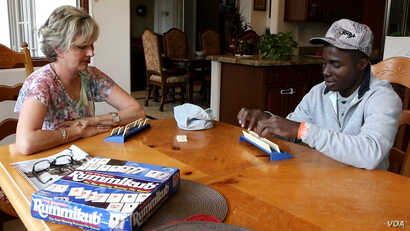 Fabrice Hampoh plays a game with his host mother in her home in Mesa, Arizona.