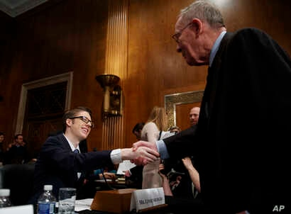 Ethan Lindenberger shakes hands with Senate Health, Education, Labor and Pensions Committee chairman, Sen. Lamar Alexander, R-Tenn., right, before the start of a  hearing on Capitol Hill in Washington,  March 5, 2019, to examine vaccines.
