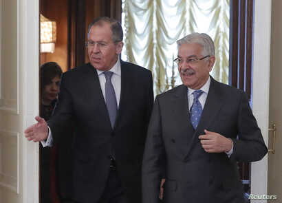 Russian Foreign Minister Sergei Lavrov, left, shows the way to his Pakistani counterpart Khawaja Asif during a meeting in Moscow, Feb. 20, 2018.